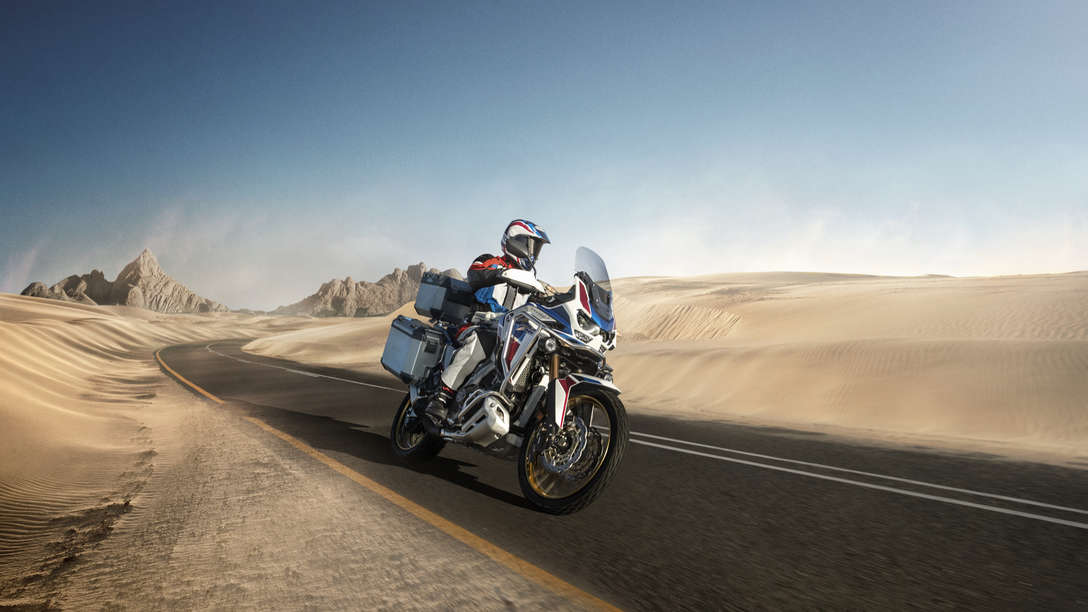 Honda Africa Twin Adventure Sports, 3-quarter front right side, riding on a road through a desert landscape